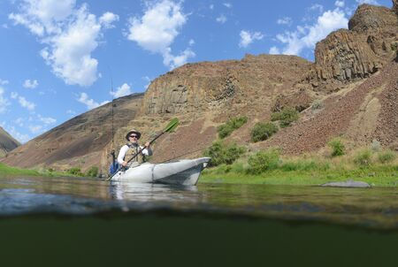 kayaker: an over under shot of many fishing while paddling in a kayak down a river with mountains in beautiful landscape  Stock Photo