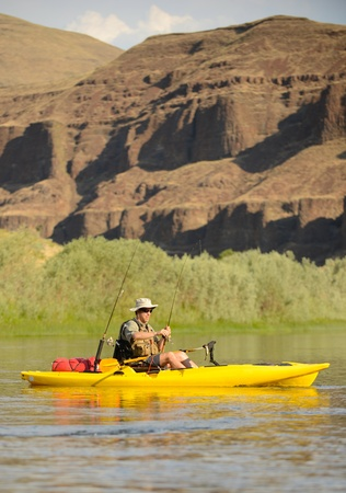 kayaker: a solitude man fishing in a kayak on a river in the summer