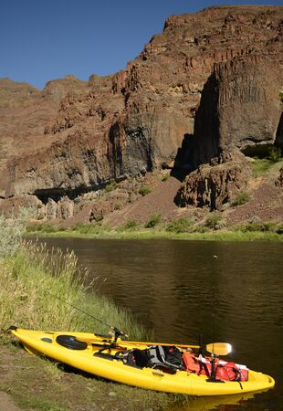 a kayak with nobody on a river in Oregon with mountains and beautiful landscape photo