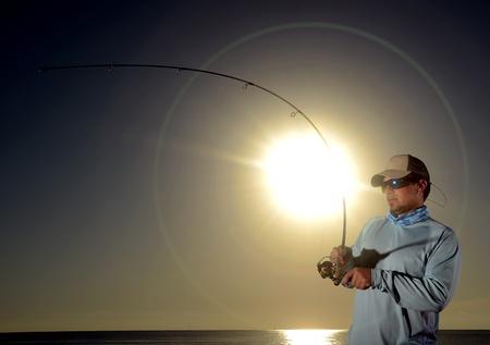 El hombre pesca con ca�a de pescar y el carrete durante el amanecer Foto de archivo