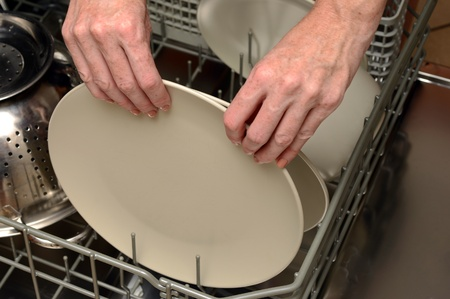 unloading: doing dishes and loading or unloading plate and a dishwasher Stock Photo