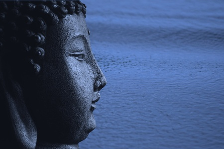 A Buddha statue in blue agains a beautiful blue ocean with ripples photo