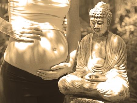 zen pregnancy with pregnant woman standing next to meditation buddha Stock fotó