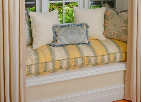A seating area in a bay window with decorative pillows and cushions in a window seat