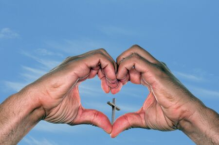 heart shape hands: Jesus is love concept with a pair of hands in a heart shape holding a cross against a blue sky