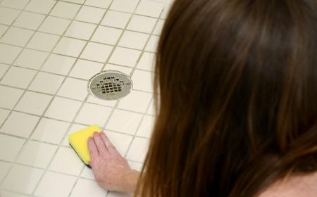 vrouw schrobben douche tegels met schuren pad om zeepresten te reinigen Stockfoto