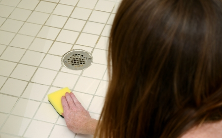 woman scrubbing shower tiles with scour pad to clean soap scum