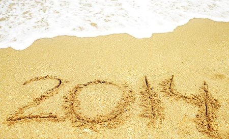 A new year 2014 written in sand on a beach photo