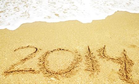 Un nuevo a�o 2014 escrito en la arena en una playa photo