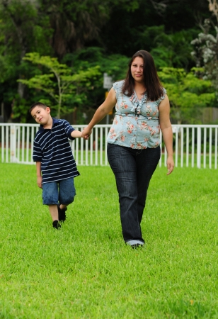 misbehaving: naughty young child in trouble with mother and dragging feet Stock Photo