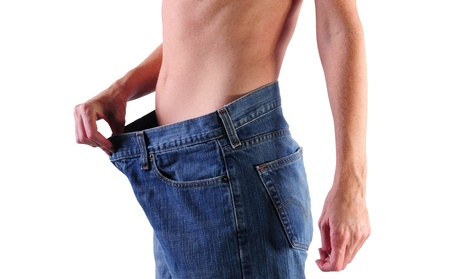 jonge gezonde vrouw in grote spijkerbroek tonen gewichtsverlies