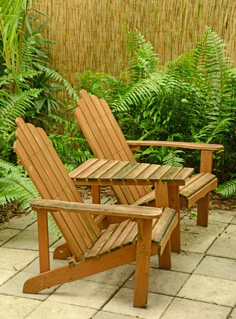 wooden Adirondack chairs in tropical backyard in summer on patio  photo