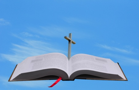 bible and cross against blue sky for heaven photo