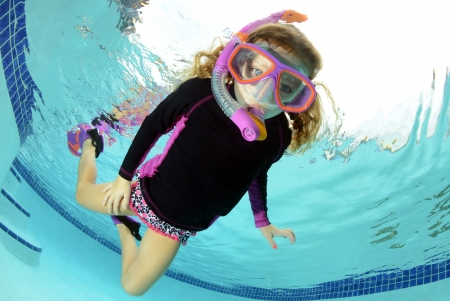 young girl swimming in pool with snorkel and goggles photo