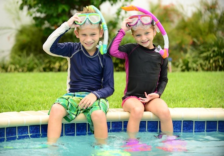 boy and girl children sitting on edge of pool ready for swimming photo