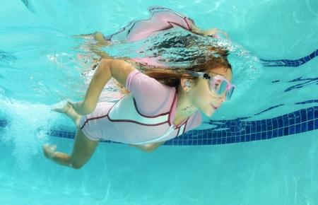 cute kid swimming underwater in pool photo