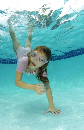 pretty young girl swimming to bottom of pool photo