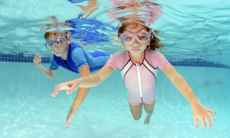 two children swimming underwater in pool in pink and blue