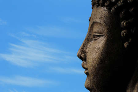 a buddha against a blue sky with clouds for meditation and enlightenment