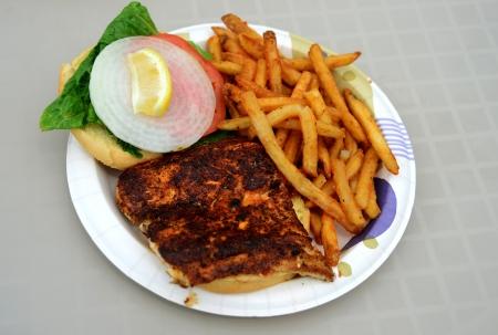 blackened mahi mahi fish sandiwch and a french fries on a plate photo