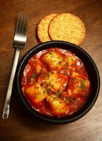 ravioli and crackers with fork on dark wood table photo