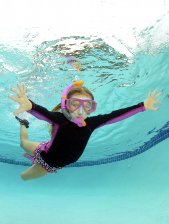 kid swimming underwater in summer in a pool photo