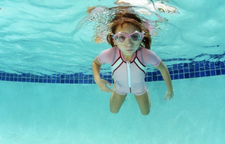 young girl holding breath underwater in swimming pool photo