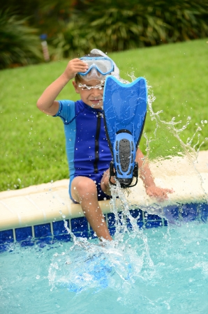 boy child splashing water with swimming flippers in summer on edge of pool photo