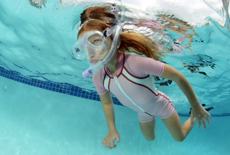 wetsuit: pretty girl swimming underwater in pool in summer Stock Photo