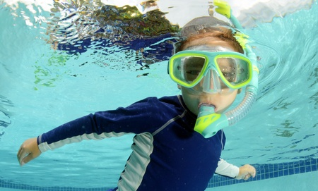 child snorkeling and swimming in pool with goggles photo