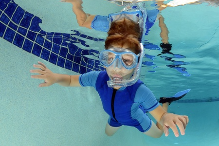 child swimming underwater in pool with goggles