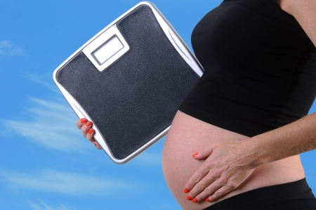 kilos: scale and weight gain during pregnancy concept  Stock Photo
