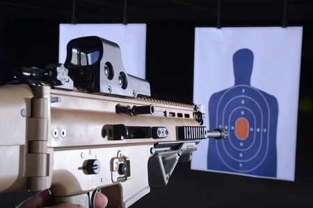 firearm or machine gun pointed at bullseye target on gun range 写真素材