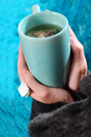 drinking tea in winter with blue mug and blanket photo