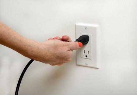 plug electric: woman with orange fingernails pulling the plug Stock Photo