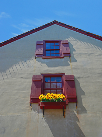 red shutters: windows with red shutters and sunflowers in medeival village Stock Photo
