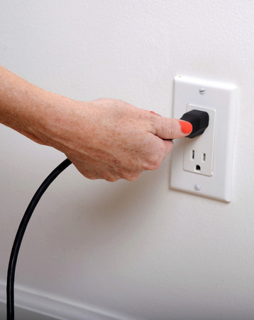 unplugging: pull the plug concept with woman pulling black cord and plug