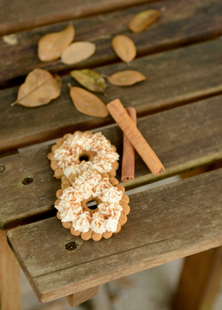 autumn dessert with nutmeg sprinkles and cinnamon sticks on white photo
