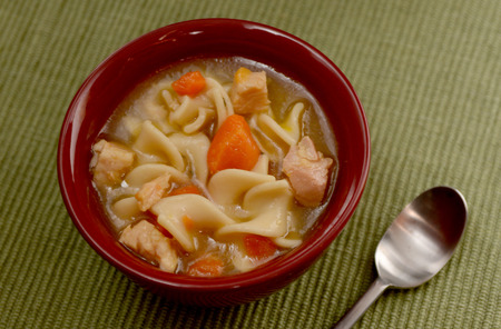 classic chicken noodle soup in red bowl photo