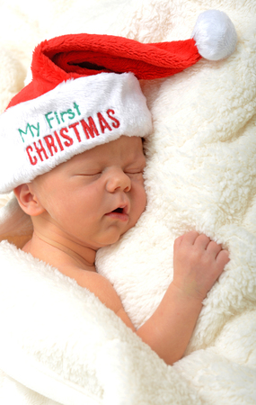 Baby's first Christmas - a newborn sleeping in a santa hat photo
