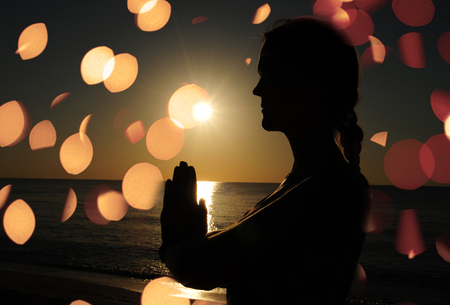 woman praying or meditating on beach photo