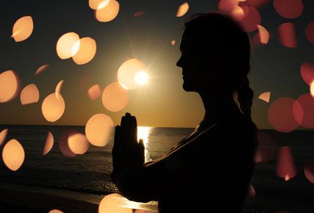 woman praying or meditating on beach photo