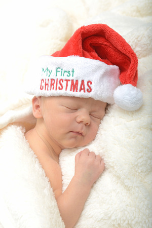 newborn infant and first Christmas in a red santa hat photo