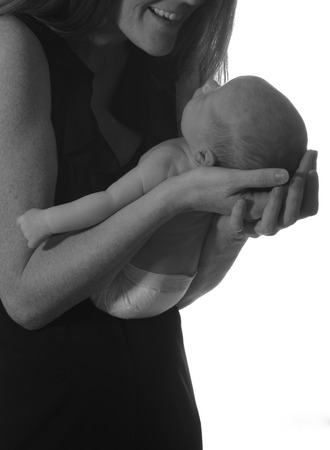 cradling: mom smiling at newborn infant and cradling baby in her arms Stock Photo