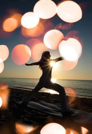 warrior II yoga pose on beach with sunrise and flares