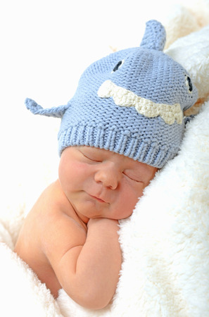 smiling newborn baby on fluffy white blanket in shark hat photo