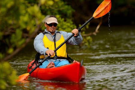 young man in kayak in a tropical location