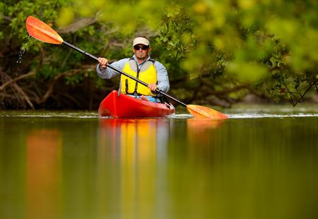 hombre joven en kayak rojo en destino tropical