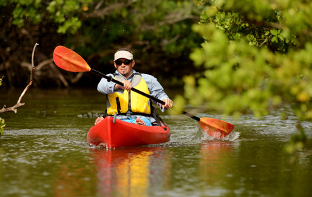 Man paddling in a red kayak in Florida