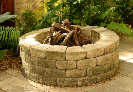 stone fire pit with bricks in the backyard Banco de Imagens